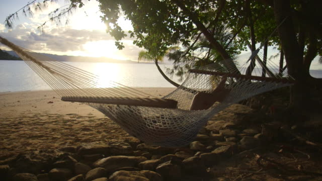 a woman rests in a hammock at sunset on a tropical island in fiji. - fiji stock videos & royalty-free footage