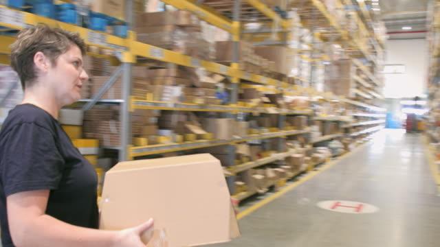 stockvideo's en b-roll-footage met vrouw terug kartonnen doos op rack in magazijn - stapelen