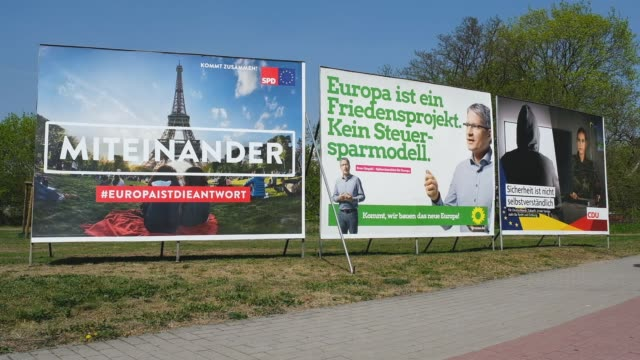 a woman rides a bicycle past election campaign billboards for european parliamentary elections of the german social democrats the german greens party... - gewerbliches schild stock-videos und b-roll-filmmaterial