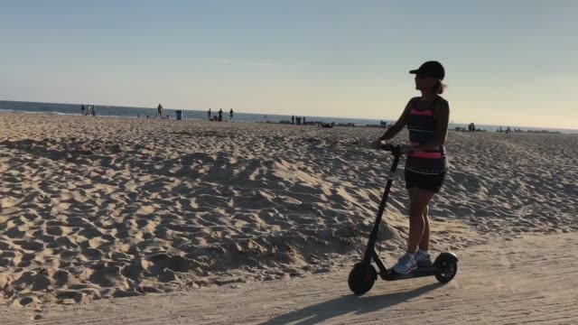 a woman rides a scooter along venice beach on august 13 2018 in los angeles california shared escooter startups bird and lime have rapidly expanded... - push scooter stock videos and b-roll footage