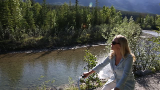Woman rides cruiser bicycle along river pathway, below mountains