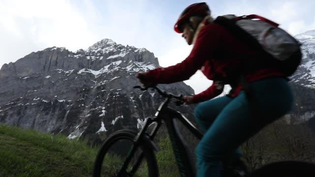 frau reitet e-bike steilen grünen wiese hang hinauf - unterwegs stock-videos und b-roll-filmmaterial