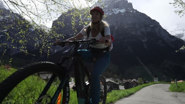 woman rides e-bike up steep mountain slope - only mature women stock videos & royalty-free footage
