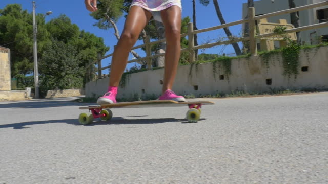 a woman rides her longboard skateboard down a hill wearing pink shoes. - slow motion - weitwinkelaufnahme stock-videos und b-roll-filmmaterial