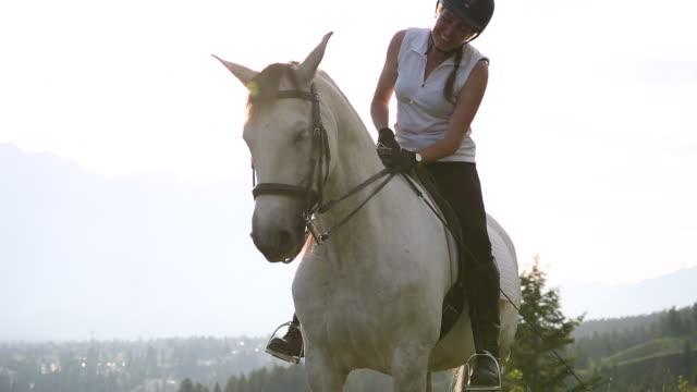 Woman rides horse across mountain meadow, sunrise