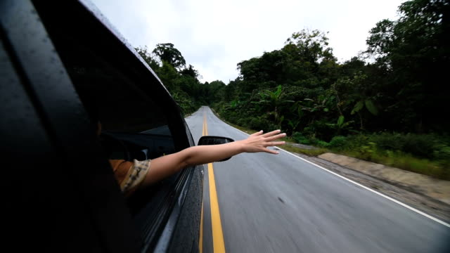woman rides in a car leaning out of the window - arms outstretched stock videos and b-roll footage