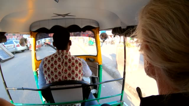 Woman rides in tuk-tuk rickshaw with driver