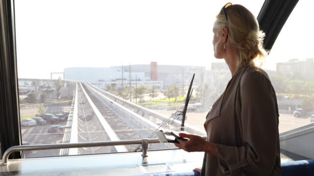 Woman rides monorail car towards airport