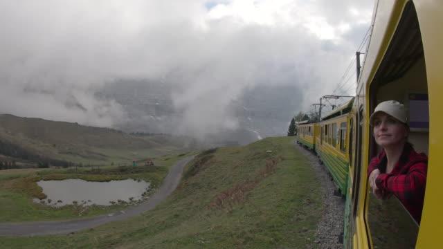 frau reitet auf dem zug entlang mountain track, sieht aus anzeigen - zugänglichkeit stock-videos und b-roll-filmmaterial