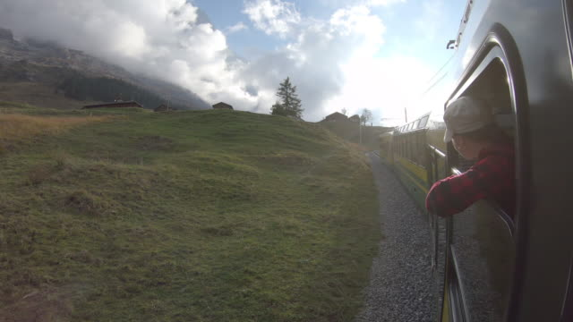 Woman rides train along mountain track, looks off to view