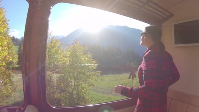 stockvideo's en b-roll-footage met vrouw rijdt trein langs berg spoor, kijkt uit naar het bekijken - alleen oudere vrouwen