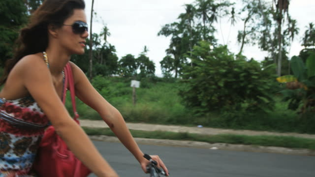 woman riding a bicycle down a costa rican road - dreiviertelansicht stock-videos und b-roll-filmmaterial