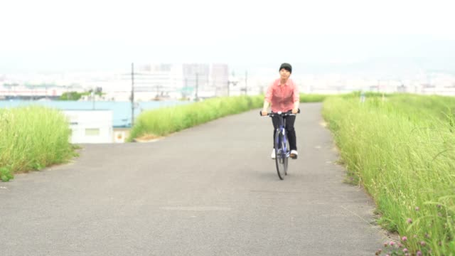 woman riding a bicycle on a road near a river - 35 39 years stock videos & royalty-free footage