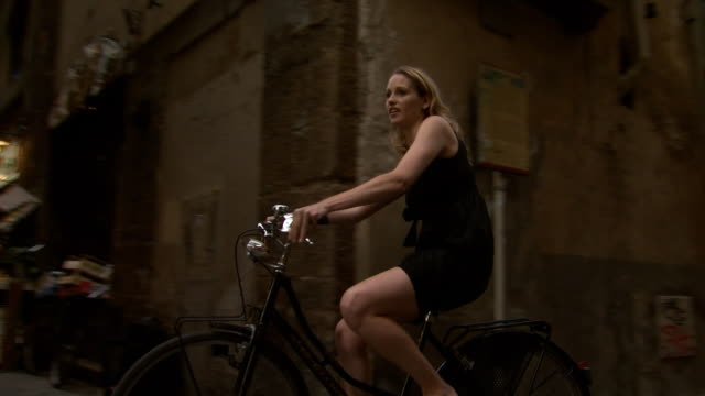 a woman riding a bike around narrow european streets - see other clips from this shoot 1150 stock videos and b-roll footage