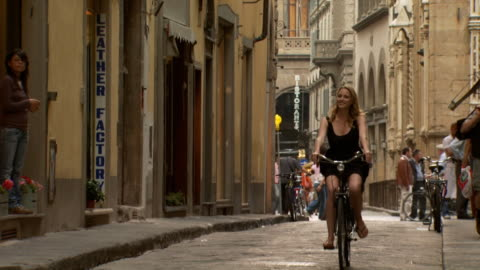 a woman riding a bike down a narrow european street - see other clips from this shoot 1150 stock videos & royalty-free footage