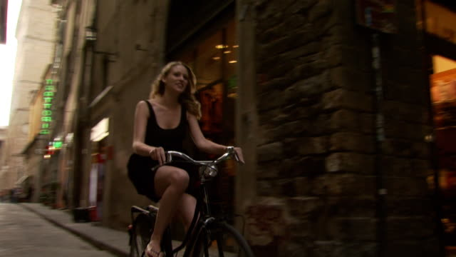 a woman riding a bike down a narrow european street - see other clips from this shoot 1150 stock videos and b-roll footage