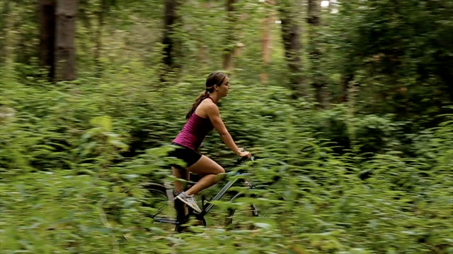 woman riding a mountain bike in the forest. - mountain bike stock videos & royalty-free footage