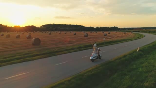 vidéos et rushes de femme d'aerial conduisant un scooter dans le pays au coucher du soleil - monter sur un moyen de transport
