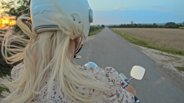 slo mo woman riding a scooter in the countryside at sunset - motor scooter stock videos & royalty-free footage