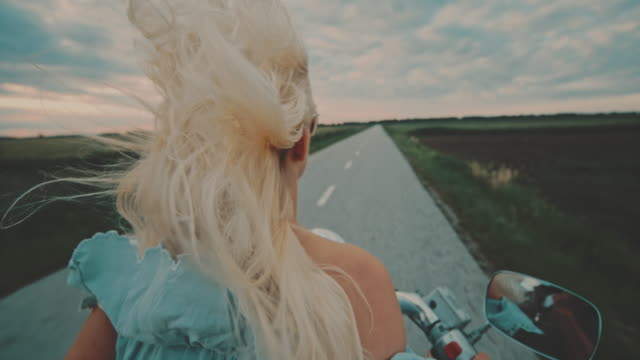 super slo mo woman riding a scooter on a country road without a helmet - super slow motion stock videos & royalty-free footage