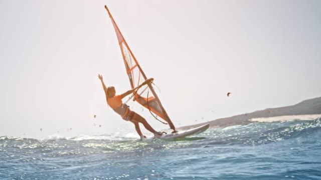 stockvideo's en b-roll-footage met slo mo vrouw een windsurf in zon rijden met één hand aan de orde gesteld in de lucht - windsurfen