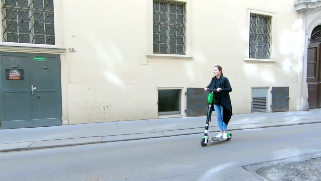 woman riding an electric scooter in vienna. austria. - motor scooter stock videos & royalty-free footage