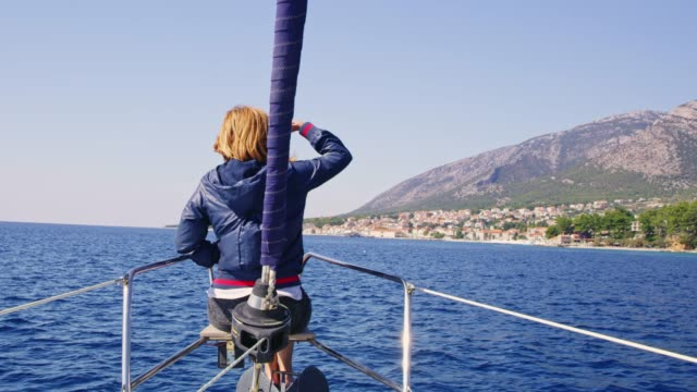 ms woman riding at bow of sailboat on sunny,tranquil ocean along bol,island of brac,croatia - bow riding stock videos & royalty-free footage