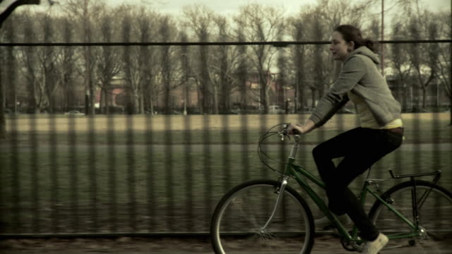 ms ts woman riding bicycle along park, brooklyn, new york city, new york state, usa - haarzopf stock-videos und b-roll-filmmaterial