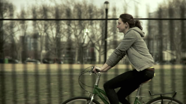 MS TS Woman riding bicycle along park, Brooklyn, New York City, New York State, USA