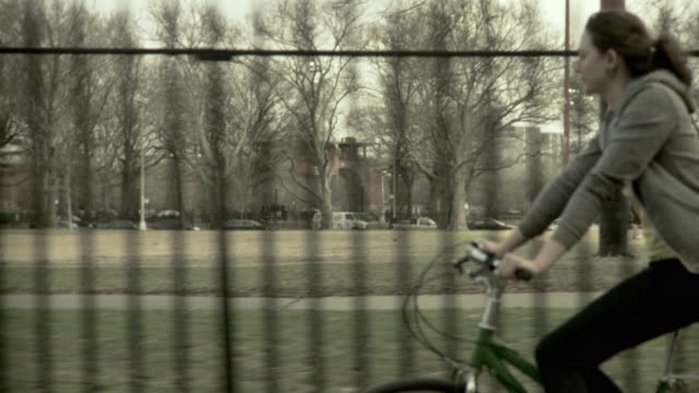 ms ts tu woman riding bicycle along park, brooklyn, new york city, new york state, usa - haarzopf stock-videos und b-roll-filmmaterial