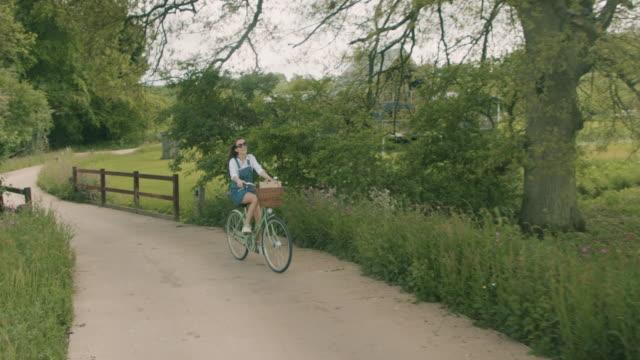 vídeos de stock e filmes b-roll de woman riding bicycle in summer - chipping norton england