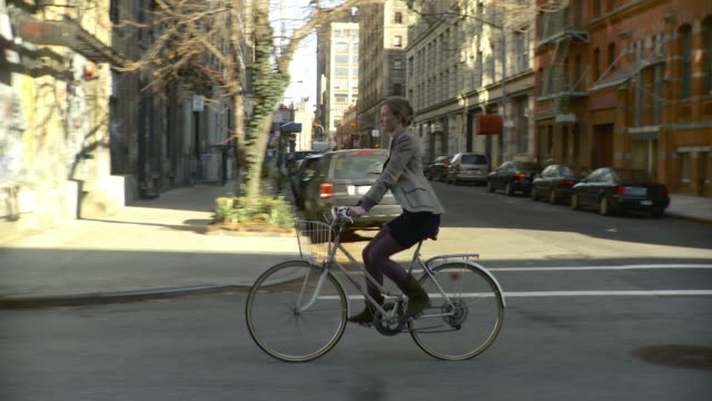 WS TS Woman riding bicycle on bike lane of street in Tribeca / New York City, New York, USA