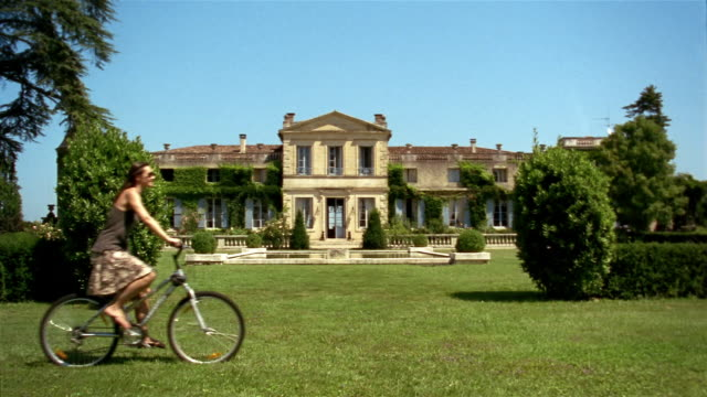Woman riding bicycle on lawn in front of chateau / Saint-Ferme, France
