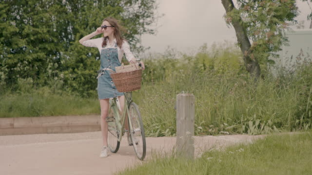 Woman riding bicycle, standing, putting sunglasses on