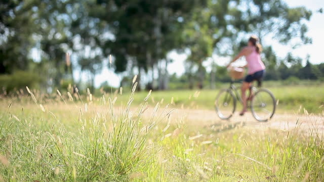Woman riding bicycle through countryside