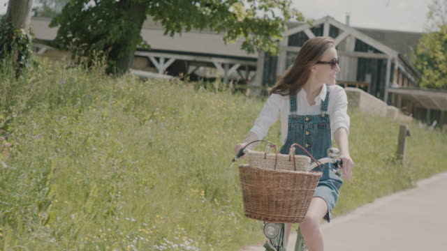 woman riding bicycle - basket stock videos and b-roll footage