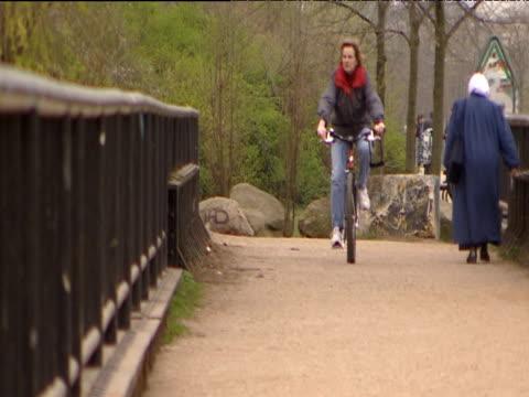 vidéos et rushes de woman riding bike across bridge towards camera past woman jogging and woman walking east berlin - joggeuse