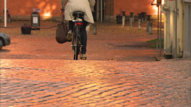 ws tu woman riding bike down cobblestone street / vaxjo, sweden - vaxjo stock videos & royalty-free footage