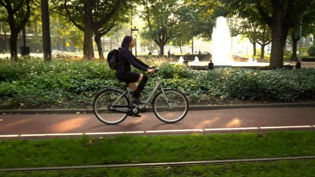 woman riding bike in park - amsterdam video stock e b–roll