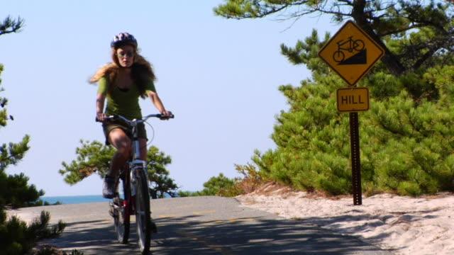 vidéos et rushes de ms, woman riding bike, provincetown, massachusetts, usa - hill