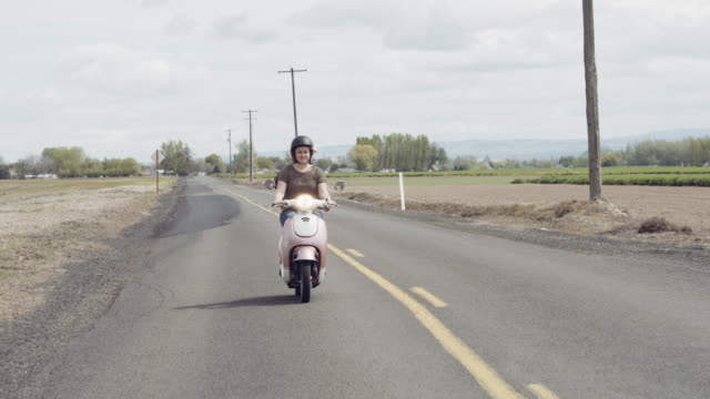 woman riding down a country road on a scooter - motor scooter stock videos & royalty-free footage