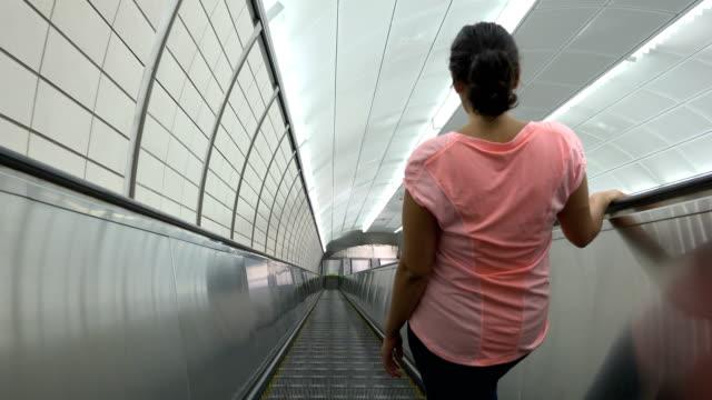Woman riding electric escalator, Subway Station, New York City