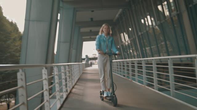 frau fährt elektro-kick-scooter auf fußgängerbrücke - motorroller stock-videos und b-roll-filmmaterial