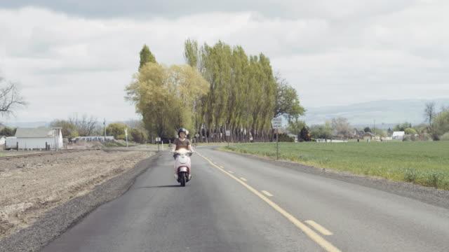 Frau Reiten Benzin Scooter auf Landstraße