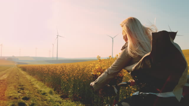 slo mo woman riding her bicycle along field of canola with wind turbines in the distance - blonde hair stock videos & royalty-free footage