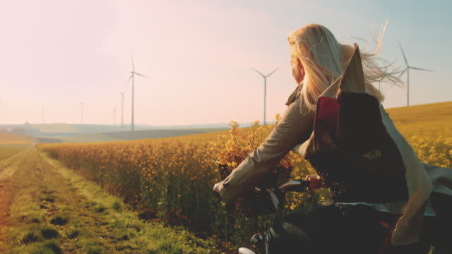 super slo mo - time warp effect woman riding her bicycle along field of canola with wind turbines in the distance - power in nature stock videos & royalty-free footage