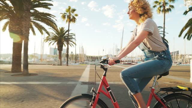 vídeos de stock e filmes b-roll de woman riding her bicycle in a beautiful sunny day. - bicicleta