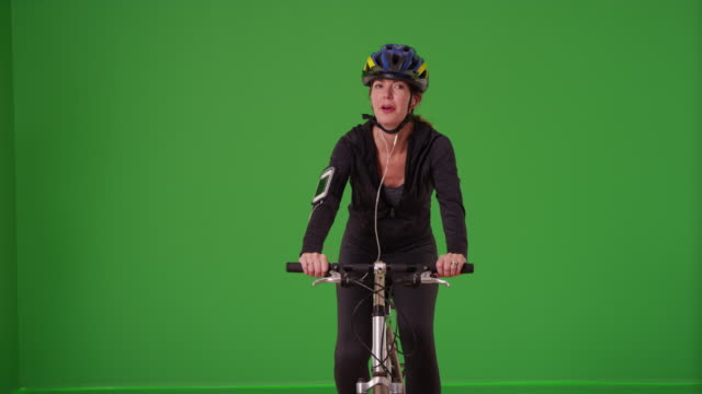 Woman riding her bicycle toward the camera with a helmet on  green screen