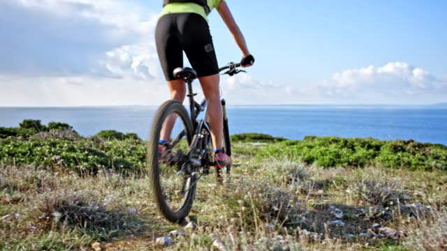 woman riding her bike down a hill with a beautiful view of the sea - mountain biking stock videos & royalty-free footage