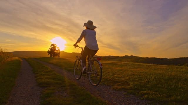 SLO MO Woman riding her bike in countryside at sunset